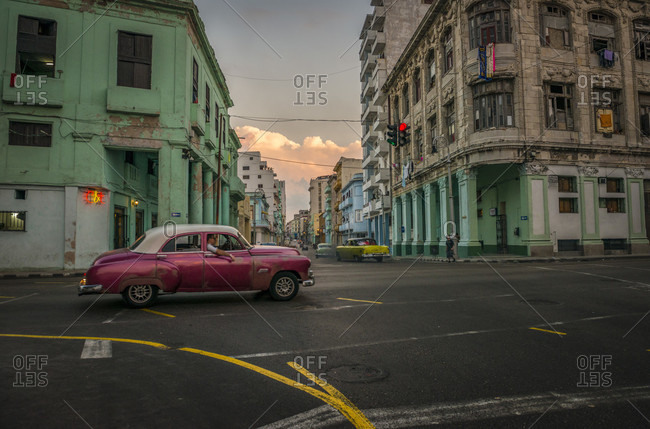 Havana, La Habana, Cuba - April 25, 2014: Colonial and modern buildings meet at the intersection of Galiano and San Lazaro in Centro Habana. A pearlescent burgundy vintage car passes through. Havana, La Habana, Cuba
