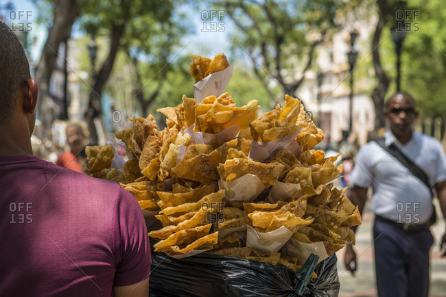 Havana, La Habana, Cuba - April 27, 2014: A street food vendor sells chiviricos (fried dough) with sugar, on El Prado Boulevard (Paseo Marti) in Centro Havana, La Habana, Cuba. Families come out on Sunday eat and admire arts and craft vendors selling their wear. A Cuban man walks by in the background