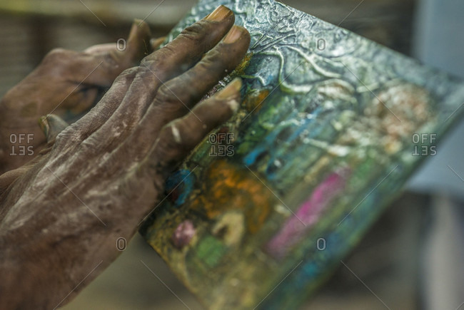 "Old Havana, La Habana, Cuba - April 28, 2014: Close-up of the hand of a Cuban artist painting in El Taller Experimental de Grafica (""Experimental Graphic Studio""), a cooperative graphic print shop in Old Havana or Habana Vieja, La Habana, Cuba"