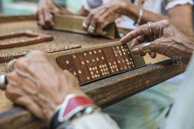 Havana, La Habana, Cuba - April 29, 2014: Elderly women playing dominoes on the street in Old Havana, La Habana, Cuba. The feisty game of dominoes is seen everywhere in Cuba and can be serious with a lot of slamming down of the pieces