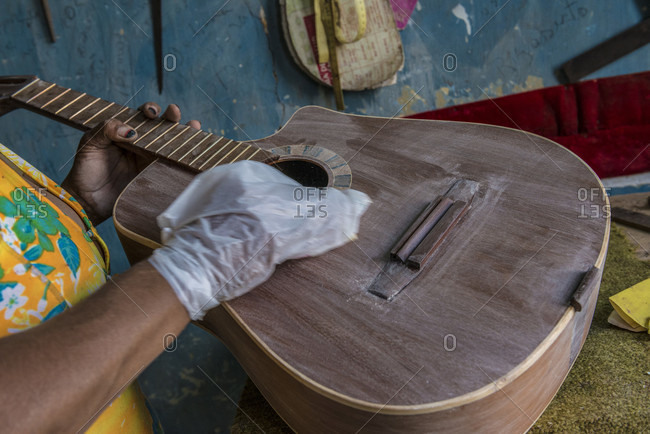 "Havana, La Habana, Cuba - April 29, 2014: A close-up the hand of a Cuban woman in the finishing stages of the guitar or ""tres"" she is working on in a hand-made guitar workshop in Havana, La Habana, Cuba"
