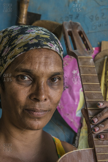 "Havana, La Habana, Cuba - April 29, 2014: A Cuban woman proudly holding the guitar or ""tres"" she is working on. It's ready for the finishing stage, in a hand-made guitar workshop in Havana, La Habana, Cuba"