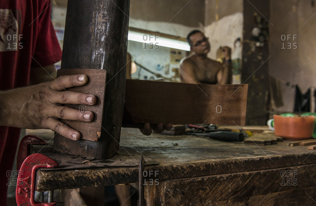 Havana, La Habana, Cuba - April 29, 2014: Close up of the hand of a young Cuban guitar-maker bending wood to shape with a hot coal-fired bending jig in a hand-made guitar workshop in Havana, La Habana, Cuba. One hand presses the wet wood against the form, and the other coaxes it into shape. His co-worker waits in the background