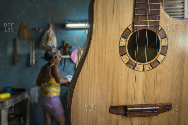 "Havana, La Habana, Cuba - April 29, 2014: A recently finished Cuban ""tres"" hangs in a hand-made guitar workshop in Havana, La Habana, Cuba. Behind it, a woman worker adds finishing touches to another one in the workshop"