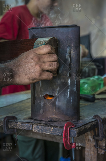 Havana, La Habana, Cuba - April 29, 2014: Close up of the hand of a Cuban guitar maker bending wood to shape with a hot coal-fired bending jig in a hand-made guitar workshop in Havana, La Habana, Cuba. One hand presses the wet wood against the form, and the other coaxes it into shape