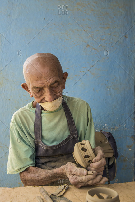 "Sancti Spiritus, Cuba - May 1, 2014: An unnamed elderly Cuban craftsman carefully sands a candle holder before glazing it at the studio of Daniel ""Chichi"" Santander, renowned Cuban potter, at the Santander Family Workshop in Trinidad, Sancti Spiritus, Cuba"