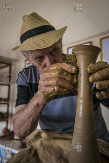 "Sancti Spiritus, Cuba - May 1, 2014: Portrait of Daniel ""Chichi"" Santander, renowned Cuban potter, intently shaping a vase on his potter's wheel. The Santander Family Workshop can be seen in the background. Trinidad, Sancti Spiritus, Cuba"