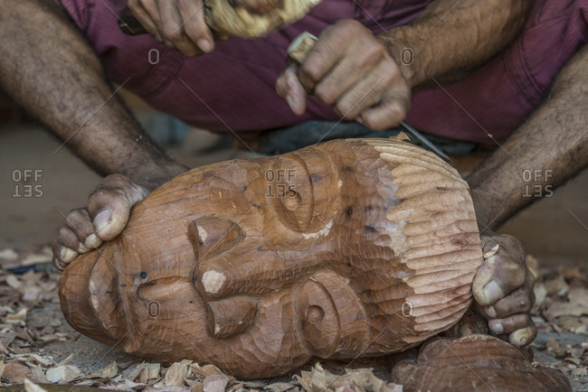 Sancti Spiritus, Cuba - October 5, 2016: A young Cuban artist is carving a decorative mask into a block of wood with a chisel, as he holds his work down with his feet. Trinidad, Sancti Spiritus, Cuba