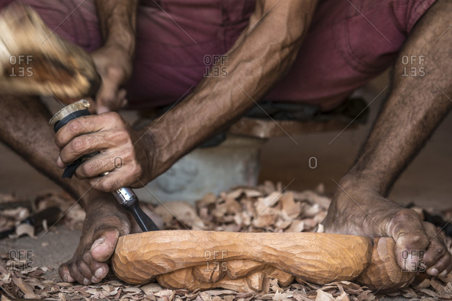 Sancti Spiritus, Cuba - May 1, 2014: A young Cuban artist is carving a decorative mask from a block of wood with a chisel, as he holds his work down with his feet. Trinidad, Sancti Spiritus, Cuba Trinidad, Sancti Spiritus, Cuba