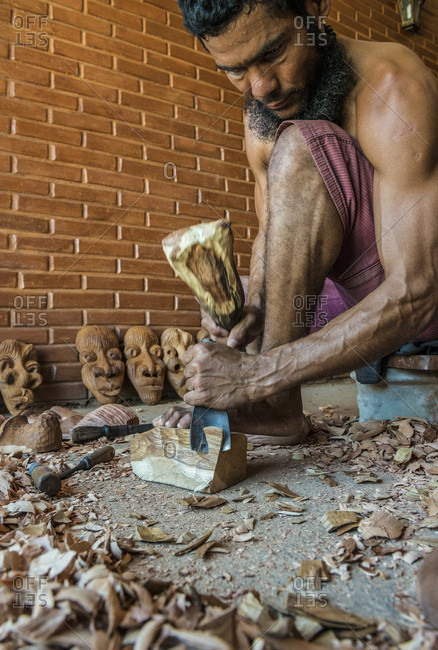 Sancti Spiritus, Cuba - May 1, 2014: A young Cuban artist is carving a decorative mask into a block of wood with a chisel as he holds his work down with his feet. His completed work can be seen in the background. Trinidad, Sancti Spiritus, Cuba