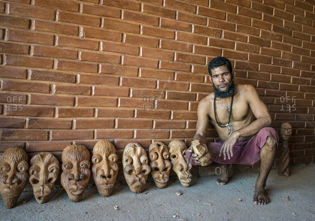 Sancti Spiritus, Cuba - May 1, 2014: A young Cuban artist shows off seven of his carved decorative masks in his workshop in Trinidad, Sancti Spiritus, Cuba. He is holding an unfinished block in his hand