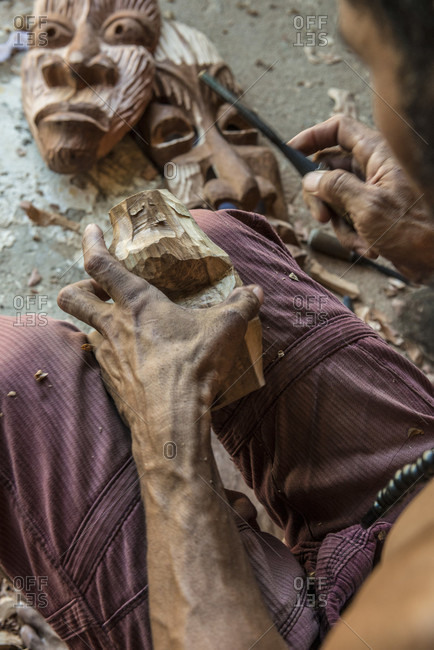 Sancti Spiritus, Cuba - May 1, 2014: A young Cuban artist is carving a decorative mask into a block of wood with a chisel. His completed work can be seen in the background. Trinidad, Sancti Spiritus, Cuba