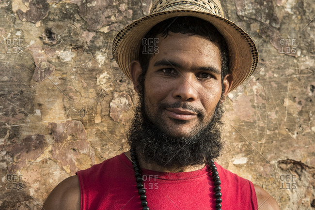 Sancti Spiritus, Cuba - April 30, 2014: A smiling young Cuban man with a beard, wearing a straw hat, black beads and a red t-shirt, stands in front of an old stone wall in Trinidad, Sancti Spiritus, Cuba