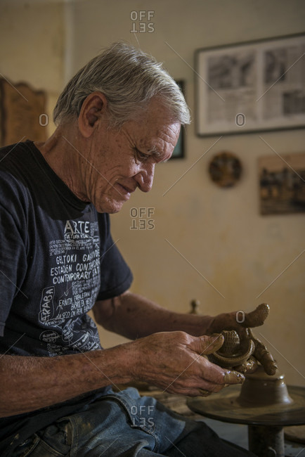 "Sancti Spiritus, Cuba - May 2, 2014: Daniel ""Chichi"" Santander, renowned Cuban potter, works on pottery that he has making at the Santander Family Workshop in Trinidad, Sancti Spiritus, Cuba. A potter's wheel sits behind him in his studio"