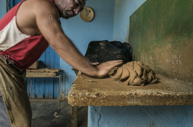 Sancti Spiritus, Cuba - May 2, 2014: A Cuban potter kneads raw clay on his workbench in Trinidad, a Cuban town well known for its pottery in the Sancti Spiritus province