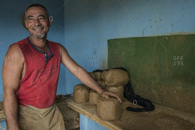 Sancti Spiritus, Cuba - May 2, 2014: A smiling Cuban potter prepares to knead and roll raw clay on his workbench in Trinidad, a Cuban town well known for its pottery in the Sancti Spiritus province