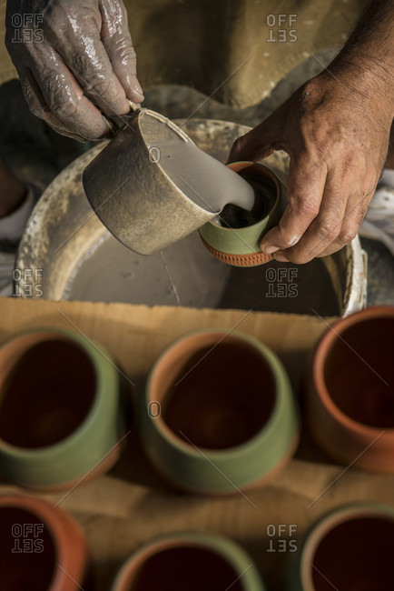 "Sancti Spiritus, Cuba - May 2, 2014: The hands of a Cuban potter pouring a glaze into a terracotta cup before firing it in a kiln. Six more cups in the foreground are awaiting this step. This cup is used to serve the traditional Cuban cocktail called the ""Canchanchara"".  Trinidad, Sancti Spiritus, Cuba"