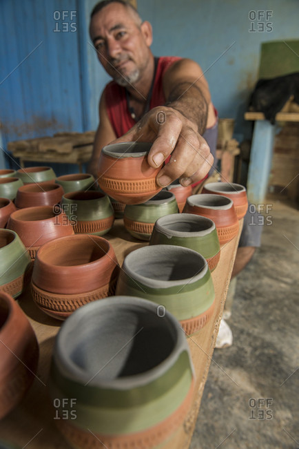 "Sancti Spiritus, Cuba - May 2, 2014: A Cuban potter places a terracotta cup in a rack. This cup is used to serve the traditional Cuban cocktail called the ""Canchanchara"".   Trinidad, Sancti Spiritus, Cuba"