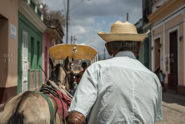 Sancti Spiritus, Cuba - May 2, 2014: An elderly Cuban carriage driver and his horse are seen from behind. Another cart and its driver precede them on the cobblestone street in Trinidad, Sancti Spiritus, Cuba