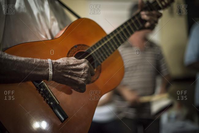 Santa Clara, Villa Clara, Cuba - May 2, 2014: A close-up of the hand of a Cuban guitarist strumming a hand-made guitar in Santa Clara, Villa Clara, Cuba
