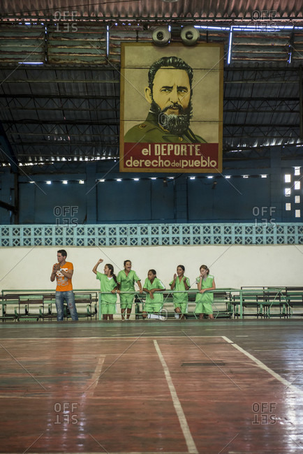"""Santa Clara, Villa Clara, Cuba - May 3, 2014: Five young girls and their coach cheer on their teammates (out of frame) during a girls indoor soccer (futbol) match. A banner depicting Fidel Castro looks on. It  Deporte - Derecho del Pueblo"""" which means, Sports - The Right of the People.  Santa Clara, Villa Clara, Cuba"""