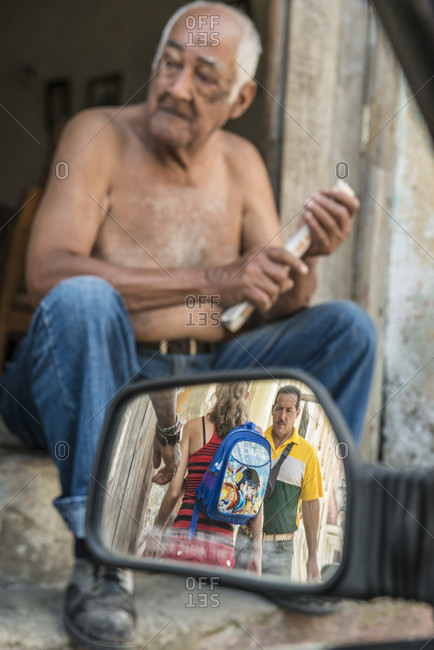 Santa Clara, Villa Clara, Cuba - May 3, 2014: An old man sitting on a step rolls up a paper while passers-by are seen walking in the car mirror in the foreground. Santa Clara, Villa Clara, Cuba