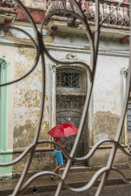 Santa Clara, Villa Clara, Cuba - May 3, 2014: Viewed through decorative iron gates, a young Cuban woman walks in the street through the rain holding a red umbrella. Santa Clara, Cuba