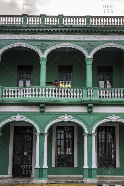 Santa Clara, Villa Clara, Cuba - May 3, 2014: Three Cuban boys laughing on an arched second floor balcony in Santa Clara, Villa Clara, Cuba