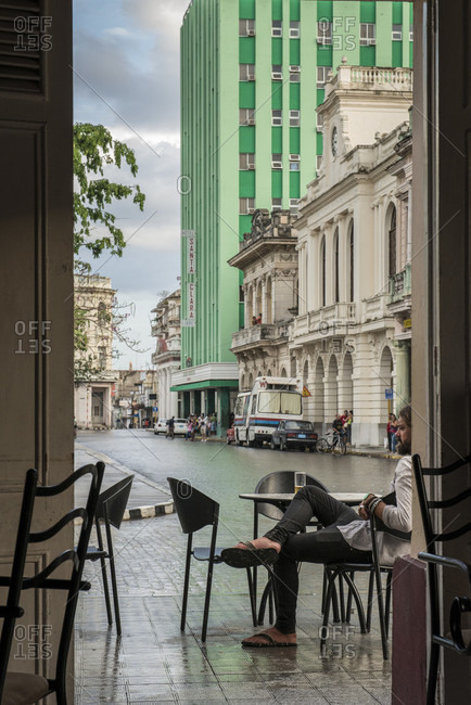 Santa Clara, Villa Clara, Cuba - May 3, 2014: A bearded young man is sitting with a beer at a cafe table in the  town square of Santa Clara, Villa Clara, Cuba during a Spring rain