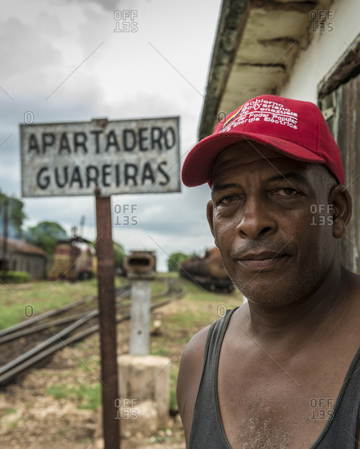 "Guareiras, Mantanzas, Cuba - October 5, 2016: Afro Cuban man wearing a red hat working at the rural Guareiras, Cuba railroad station. Behind him the sign reads ""Apartadero Guadeiras"" indicating the rail siding there. The siding is visible behind him"