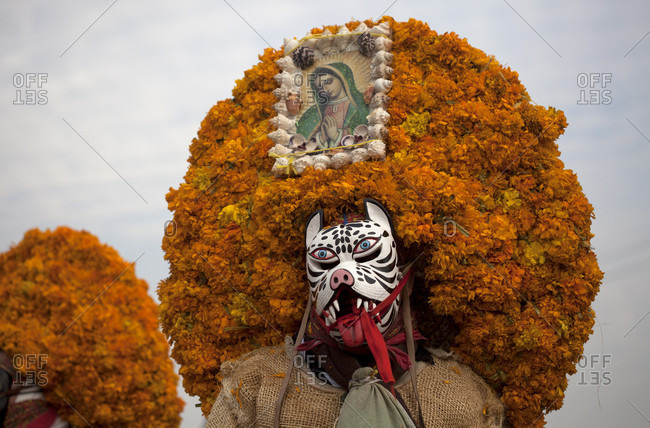 """Mexico City, Mexico - December 10, 2015: Tlacololeros de Carrizalillo, Guerrero, wearing sombreros covered by flowers dance during the annual pilgrimage to the Basilica of Our Lady of Guadalupe, Tepeyac Hill, Mexico City, Mexico. Guadalupe is known for indigenous as Tonantzin, that means """"Our Mother"""" in Mexican nahuatl language. Millions arrive every year to the pilgrimage"""