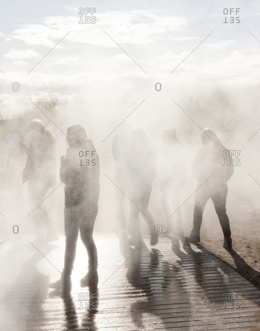 Geyser geothermal area, Iceland - March 31, 2013: Tourists standing in steam at Geyser geothermal area, south Iceland