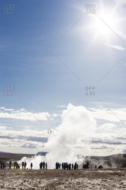 Geyser geothermal area, Iceland - March 31, 2013: People looking at Strokkur geyser erupting at Geyser geothermal area, South Iceland