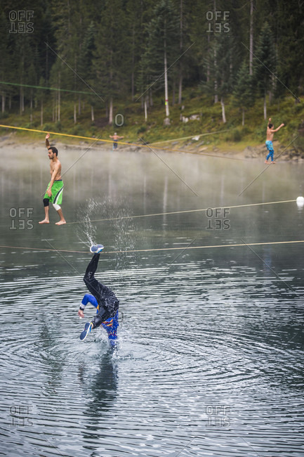 Flims, Switzerland - September 6, 2015: Slack liners on a multiple lines over the water at lake Cauma in Flims, Switzerland in an early morning session. This took place at the annual waterline tour organized by the Swiss Salcklien Association