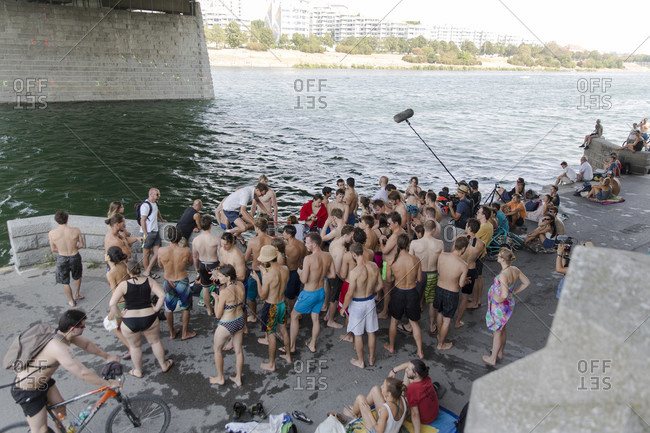 """Vienna, Austria - August 8, 2015: Impressions from the annual Urban boulder cup in Vienna. This event returned for the second time to the """"Reichsbrucke"""" at the New Danube Channel. Athletes compete in a deep water solo climbing competition style against each other on preset routes. The height of the climbing wall is about 10 meters and any mistakes is automatically leading to a fall in the refreshing water"""