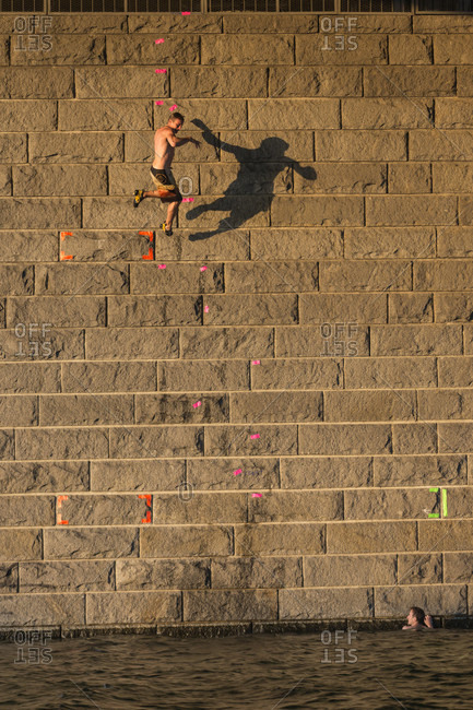 """Vienna, Austria - August 8, 2015: Impressions from the annual Urban boulder cup in Vienna. This event returned for the second time to the """"Reichsbrucke"""" at the New Danube Channel. Athletes compete in a deep water solo climbing competition style against each other on preset routs. The height of the climbing wall is about 10 meters and any mistakes is automatically leading to a fall in the refreshing water"""
