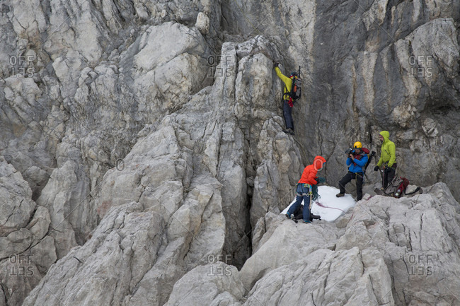Dachstein, Styria, Austria - June 18, 2015: Professional highline athlete Reinhard Kleindl and his crew on a special alpine highline project in the Austrian alps. This project is set almost at 3000 meters above see level. The project involves a difficult climbing access as well as special rigging skills