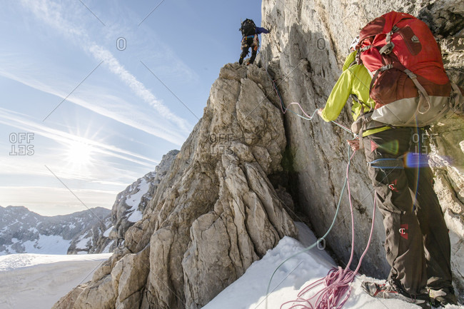 Dachstein, Styria, Austria - June 30, 2015: Professional highline athlete Reinhard Kleindl and his crew on a special alpine highline project in the Austrian alps. This project is set almost at 3000 meters above see level. The project involves a difficult climbing access as well as special rigging skills