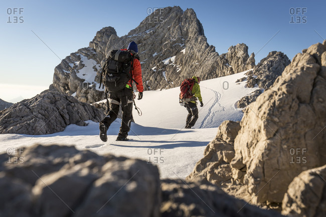 Dachstein, Styria, Austria - July 1, 2015: Professional highline athlete Reinhard Kleindl and his crew on a special alpine highline project in the Austrian alps. This project is set almost at 3000 meters above see level. The project involves a difficult climbing access as well as special rigging skills