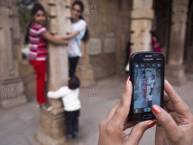 New Delhi, New Delhi, India - July 4, 2015: Woman photographing friends using mobile camera at Qutub Minar, New Delhi, India