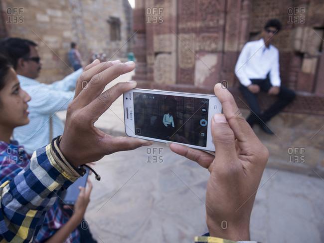 New Delhi, New Delhi, India - July 4, 2015: Friends photographing using mobile camera at Qutub Minar, New Delhi, India