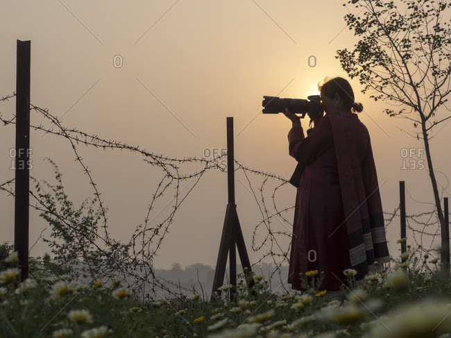 Agra, Uttar Pradesh, India - July 4, 2015: Silhouette of woman photographing, Agra, Uttar Pradesh, India