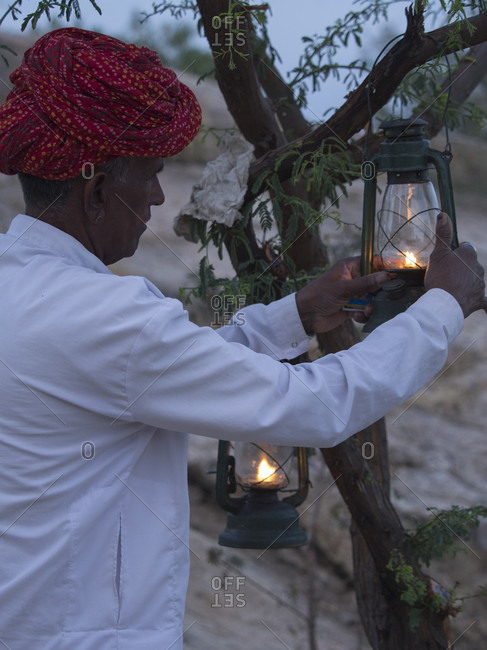 Chhatrasagar, Rajasthan, India - July 4, 2015: Man in turban hanging oil lamp on tree in  Chhatrasagar, Rajasthan, India