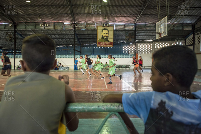 "Santa Clara, Villa Clara, Cuba - May 3, 2014: Two young Cuban boys look on during a girls indoor handball match. A banner depicting Fidel Castro looks on. It reads, ""El Deporte - Derecho del Pueblo"" which means, Sports - ""The Right of the People"".  Santa Clara, Villa Clara, Cuba"