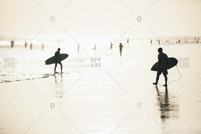 Silhouette of men walking with surfboard on Berawa Beach