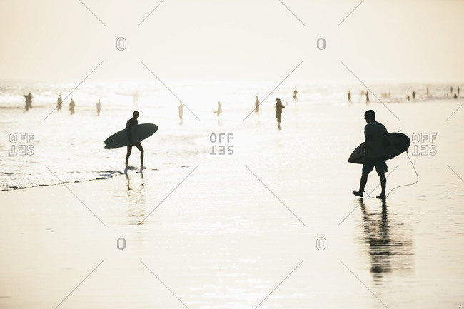 Silhouette of men walking with surfboard on Berawa Beach