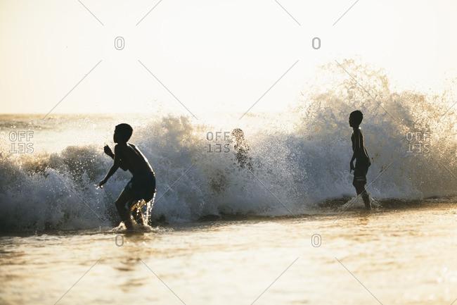 Children playing in crashing waves on Berawa Beach