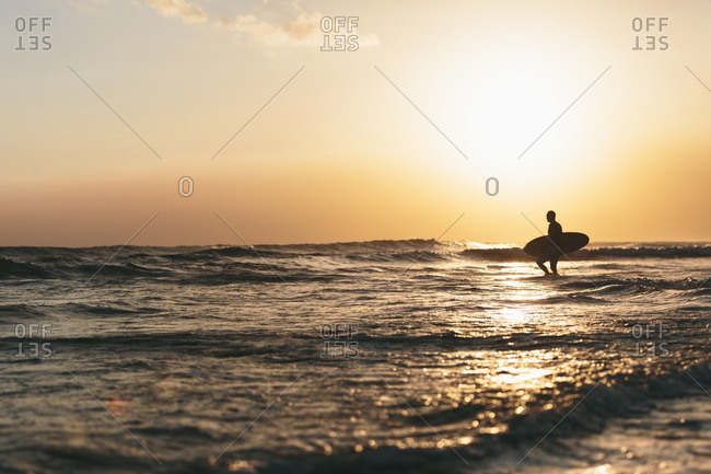 Man walking with surfboard in the waves at Berawa Beach