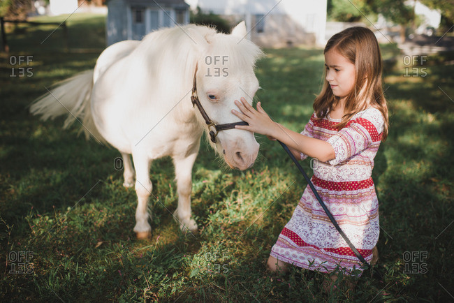Young girl sitting and petting a small white pony on a farm