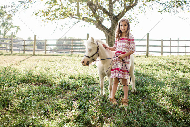 Young girl standing with a white pony on a farm